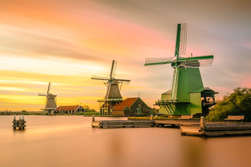 The beautiful Zaanse Schans at sunset. Zaanse Schans is an amazing day trip from Amsterdam, where you'll be able to admire the traditional Dutch windmills